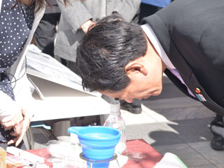 堀田の勧めでペットボトル顕微鏡を覗く下村文部科学大臣